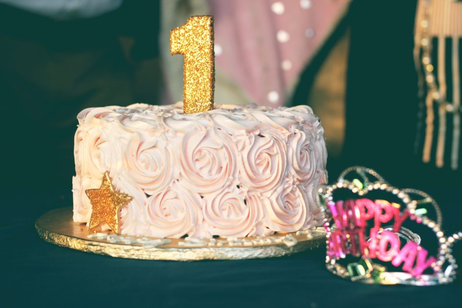 Pink birthday cake with a gold glitter number 1 on it